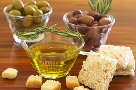 Two jars of green and black olives with stick of rosemary, croutons and slices of wholewheat bread on wooden table background photo