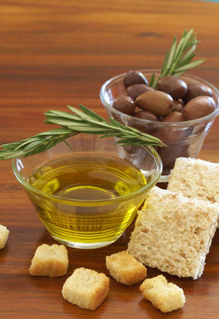 Two jars of black olives with stick of rosemary, olive oil, wholewheat bread and croutons on wooden table background photo