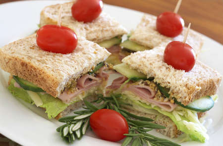 wholegrain mustard: Tasty club sandwich with green lettuce, cheese, smoked ham and wholegrain mustard on wholewheat bread with rosemary and tomatoes on white plate Stock Photo
