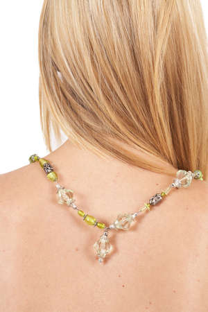Beautiful blonde woman with long hair wearing green necklace isolated on white background photo