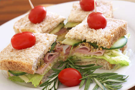 wholegrain mustard: Tasty club sandwiches with green lettuce, grated cheese, smoked ham and wholegrain mustard on wholewheat bread with rosemary and tomatoes  Stock Photo