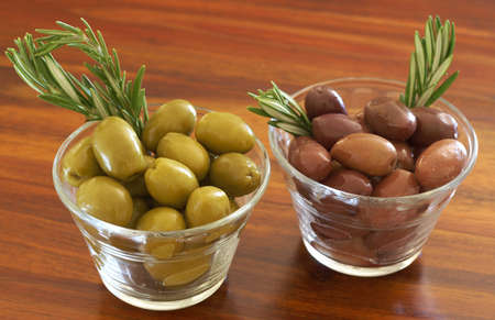 Two jars of green and black olives with stick of rosemary on wooden table background photo