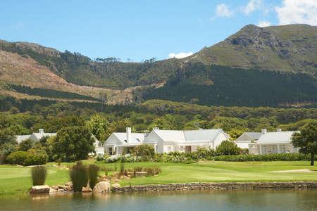 Paisaje de campo de golf con pocas casas en las montañas en un día de verano hermoso  Foto de archivo - 4235284