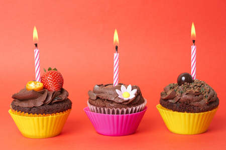 Three miniature chocolate cupcakes with icing, decorations and birthday candles on red background Stock Photo