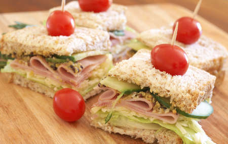 wholegrain mustard: Tasty club sandwich with green lettuce, grated cheese, smoked ham, cucumber and wholegrain mustard on wholewheat bread with tomatoes on chopping board Stock Photo