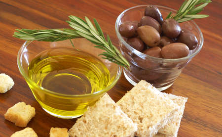 Two jars of black olives with stick of rosemary, olive oil, slices of bread and croutons on wooden table background photo