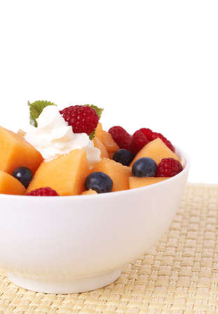 Bowl of summer fruit salad with raspberries, melon, blueberries, cream and mint leaves in a white bowl isolated photo