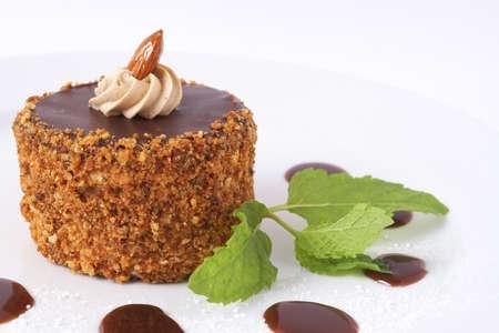Miniature meringue gâteau au chocolat avec de la crème et des amandes, servi sur un plateau décoré avec des feuilles de menthe, du chocolat et de boîtes de sucre glace Banque d'images - 4455404