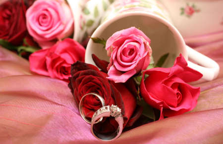 Small bouquet of red and pink roses in a vase with two wedding rings. Very shallow depth of field, macro shot Stock Photo - 4603708