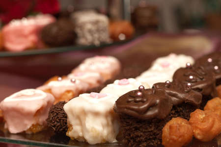 Selection of miniature petit-fours - coconut, chocolate cream, strawberry and vanilla cakes on glass plate Stock Photo - 4603715