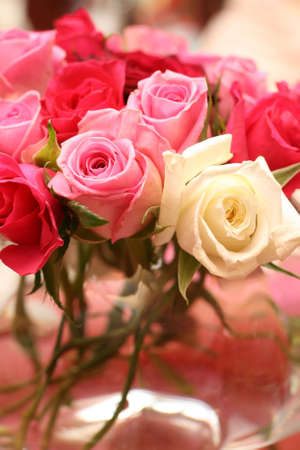 Small bouquet of red, white and pink roses in a vase at the wedding. Very shallow depth of field, macro shot