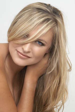 Portrait of a beautiful blonde woman with light blue eyes and natural make-up on grey background