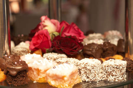 dainty: Selection of miniature petit-fours - coconut, chocolate cream and vanilla cakes on glass plate with roses
