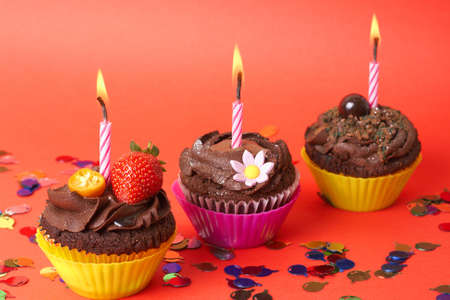 Miniature chocolate cupcakes with icing, decorative flower, strawberry and birthday candles on red background with decorations photo