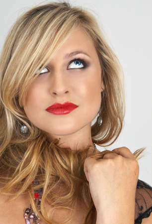 Portrait of a beautiful blonde woman with light blue eyes and evening make-up on grey background photo