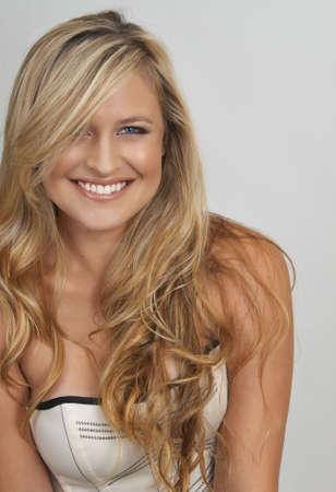 blonde yeux bleus: Portrait d'une belle femme blonde aux yeux bleu clair et naturel du maquillage sur le port d'un corset, fond gris Banque d'images