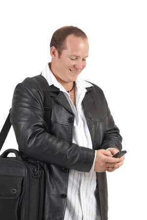 Young successful businessman wearing leather jacket smiling at a message on his cellphone. Isolated on white background photo