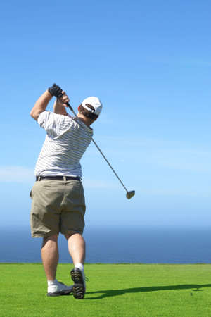 Young male golfer hitting the ball from the tee box next to the ocean on a beautiful summer day  photo