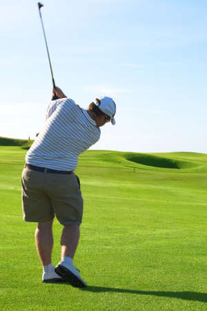 Young male golfer hitting the ball from the fairway on a beautiful summer day  photo