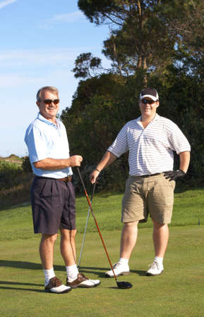 Young male golfer with his senior father ready to tee off on a beautiful summer day  Stock Photo