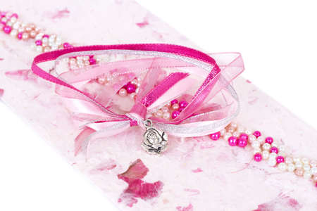 Beautiful pink wedding invitation with ribbons and beads on textured paper isolated on white background with copy space photo