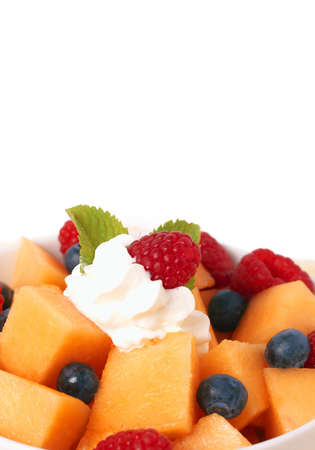 Bowl of summer fruit salad with raspberries, melon, blueberries, cream and mint leaves in white bowl