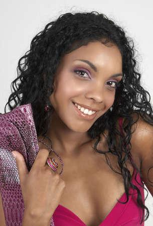 cocktaildress: Mooie brunette vrouw het dragen van roze cocktail jurk en accessoires glimlachen op witte achtergrond. Niet geïsoleerd