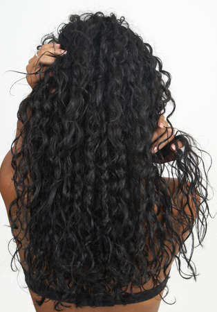Beautiful brunette woman showing off her long curly hair on white background. Not isolated