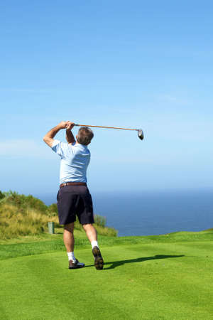 Senior male golfer playing golf from the tee box facing the ocean on a beautiful summer day photo