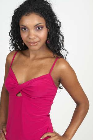 cocktaildress: Mooie brunette Afrikaanse vrouw dragen van roze cocktail jurk en accessoires glimlachen op witte achtergrond. Niet geïsoleerd  Stockfoto