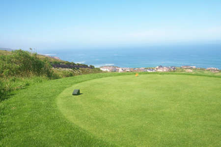 Golf course landscape with few houses by the ocean on a beautiful summer day photo