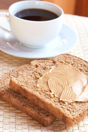 Two slices of Tasty healthy wholewheat bread with peanut butter spread and cup of black coffee on the table Stock Photo