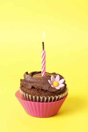 Miniature chocolate cupcake with icing, decorative flower and birthday candle on yellow background photo