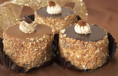 Miniature chocolate meringue cakes with cream, chocolate coffee bean and almonds photo
