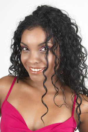 cocktaildress: Mooie brunette vrouw het dragen van roze cocktail jurk glimlachend op lichte achtergrond. Niet geïsoleerd