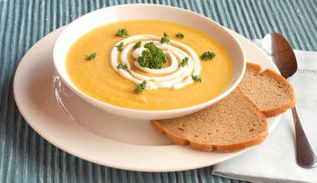 Bowl of fresh hot butternut soup with cream and parsley, served with rye berliner bread Stock Photo - 8901341