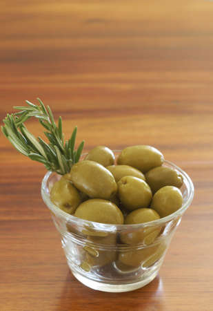 Jar of green olives and rosemary on wooden table background photo