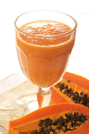 papaya: Glass of fresh papaya smoothie with sliced papaya