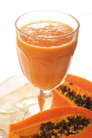Glass of fresh papaya smoothie with sliced papaya