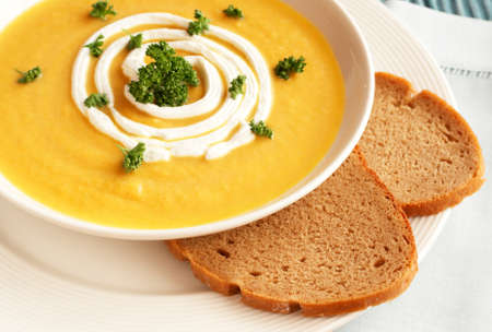 pumpkin leaves: Bowl of fresh hot butternut soup with cream and parsley, served with rye berliner bread