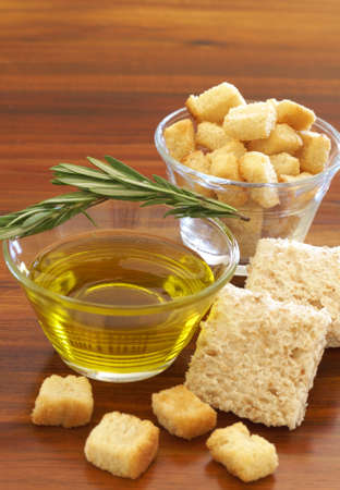 Two jars of olive oil with stick of rosemary and croutons on wooden table background photo