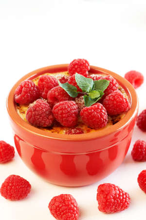 French creme brulee dessert with raspberries and mint covered with caramelized sugar in red terracotta ramekin on white background photo