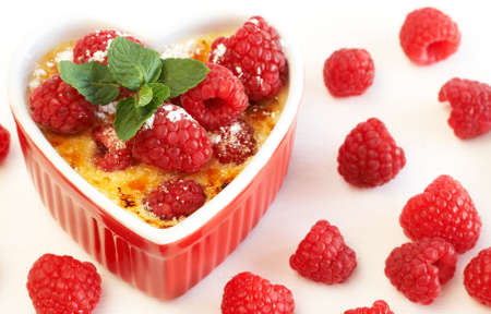 French creme brulee dessert with raspberries and mint covered with caramelized sugar in red terracotta heart ramekin on white background