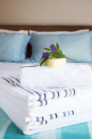 bed linen: Beautiful bedroom interior with white sheets and striped towels with soap and flowers