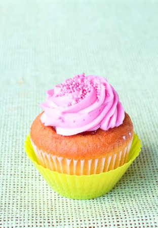Freshly baked strawberry and vanilla cupcake on green background photo