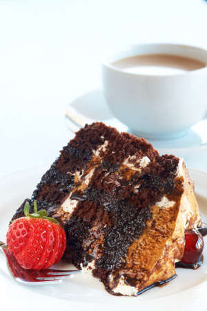Slice of Black Forest cake with fresh cream and cherries, served on a white plate with silver fork and a cup of coffee photo