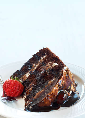 Slice of Black Forest cake with fresh cream and cherries, served on a white plate with silver fork and strawberry photo