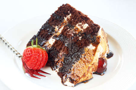 Slice of Black Forest cake with fresh cream and cherries, served on a white plate with silver fork
