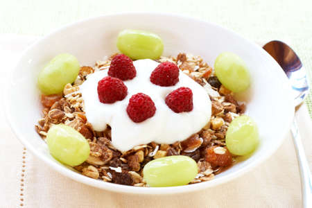 fruity salad: Healthy breakfast with muesli, fresh yoghurt, grapes and raspberries