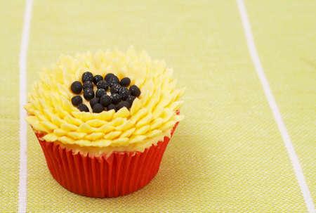 buttercream: Fresh vanilla cupcake with sunflower buttercream icing decoration on green background